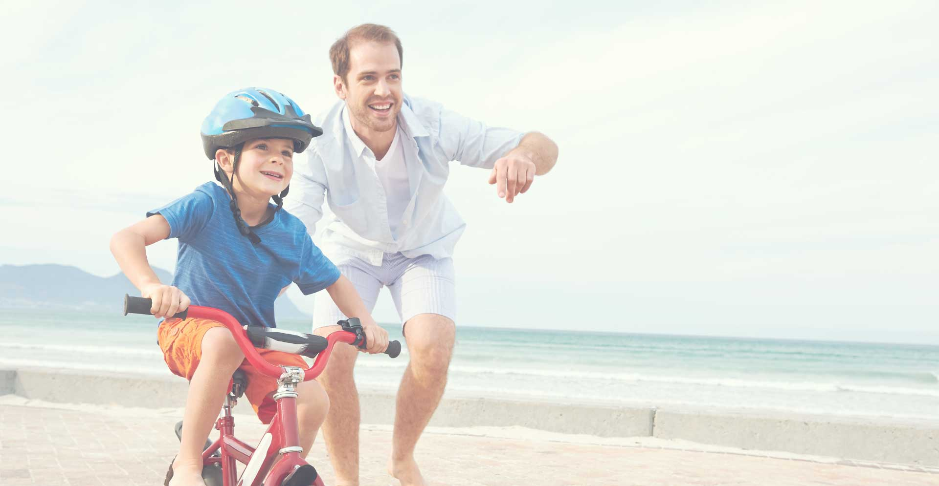 dad-and-son-on-bike-at-the-beach-image-treovir